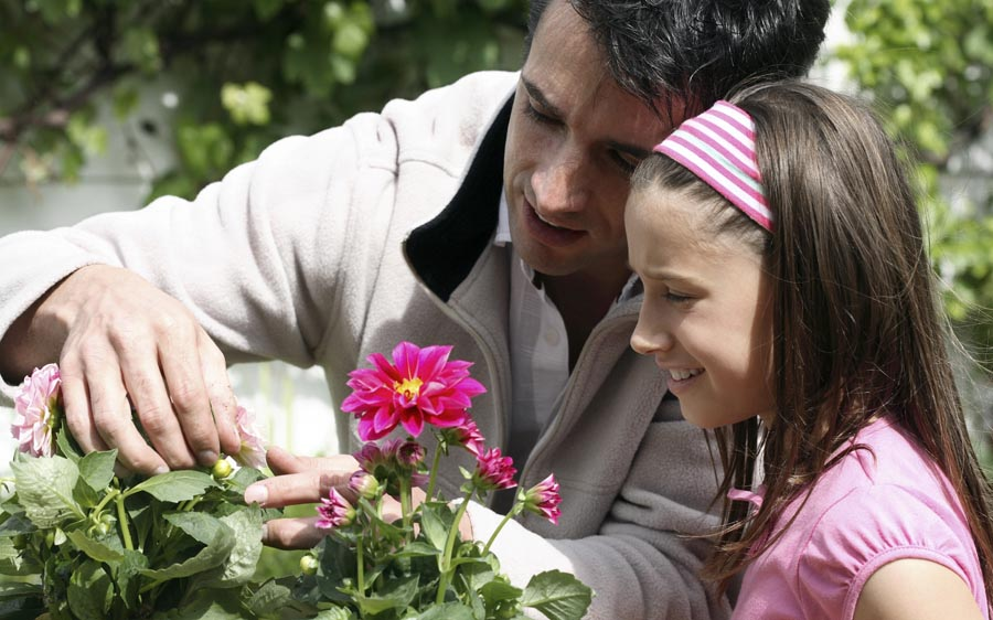 Father and daughter looking at plants
