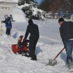 People shovelling snowy yard
