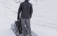 Main walking in snow with snow blower