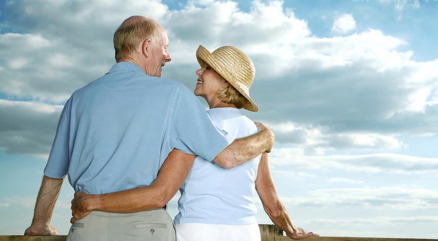 Two older people with clouds in background