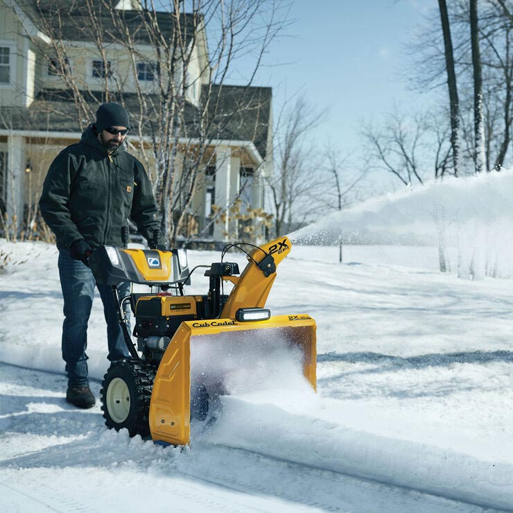 Man using snow thrower in front of home