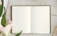 Open book with flower next to it