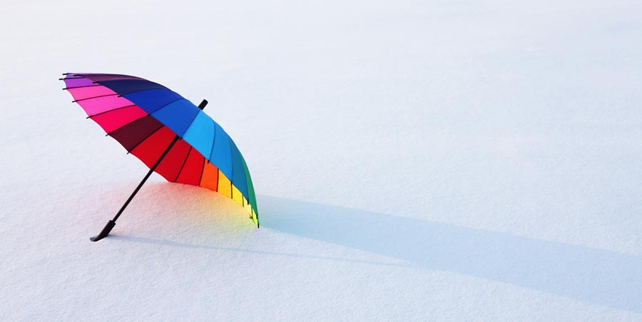 Colorful umbrella on snow covered ground