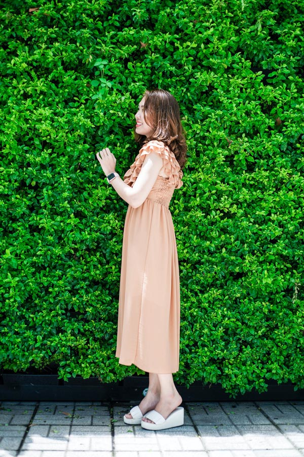 Person standing in front of hedge