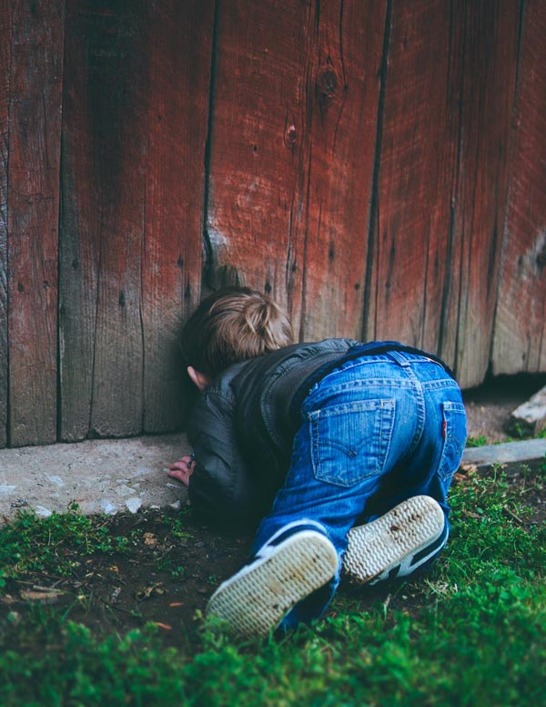 Boy looking through hole in fence