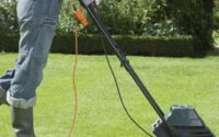 Woman Mowing Lawn With electric Lawn Mower
