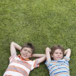 Portrait of two boys (6-11) lying on grass, hands behind head
