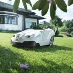 Robotic lawn mower on lawn in front of house