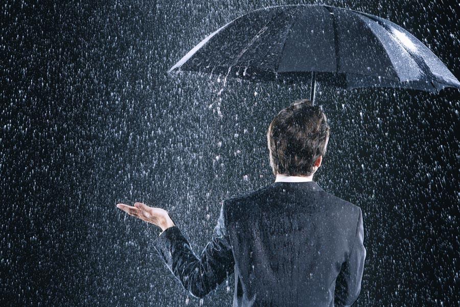 Main under umbrella with heavy rain failling