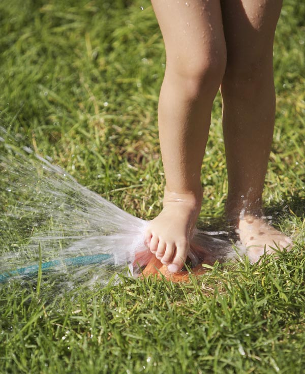 South Africa, Cape Town, girl playing with lawn sprinkler