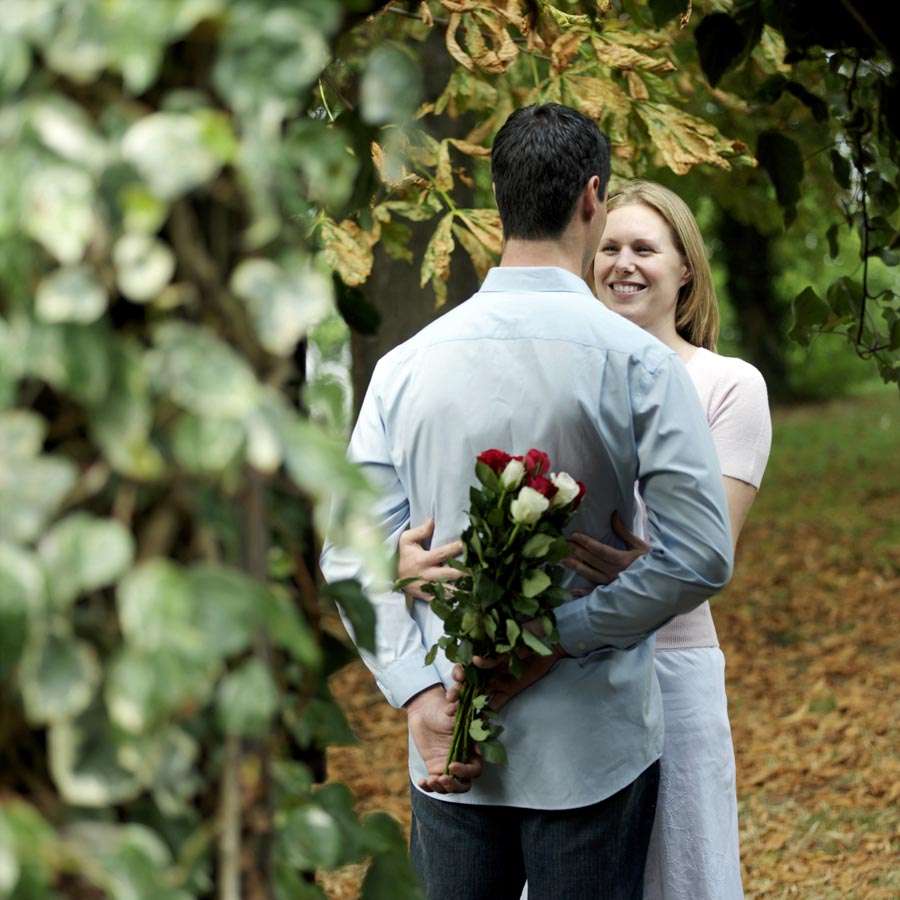 Man and woman with man holding roses behind his back