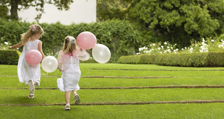 Two girls with balloons running away from camera