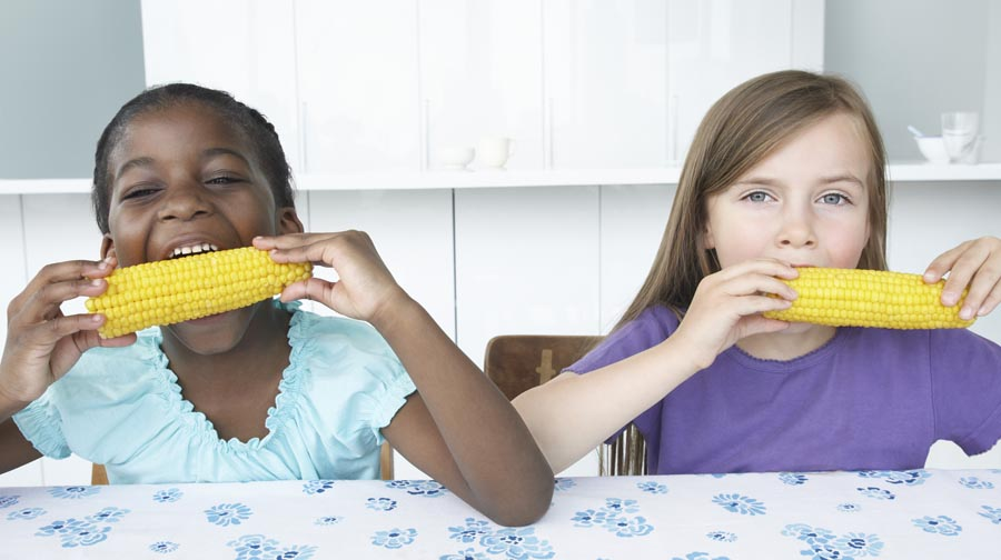 Two Girls Eating Corn on the Cob
