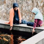 Two females sitting by pond pointing at fish