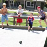 Children looking excited playing Bocce Ball