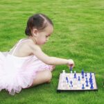 Baby playing chess with teddy on lawn