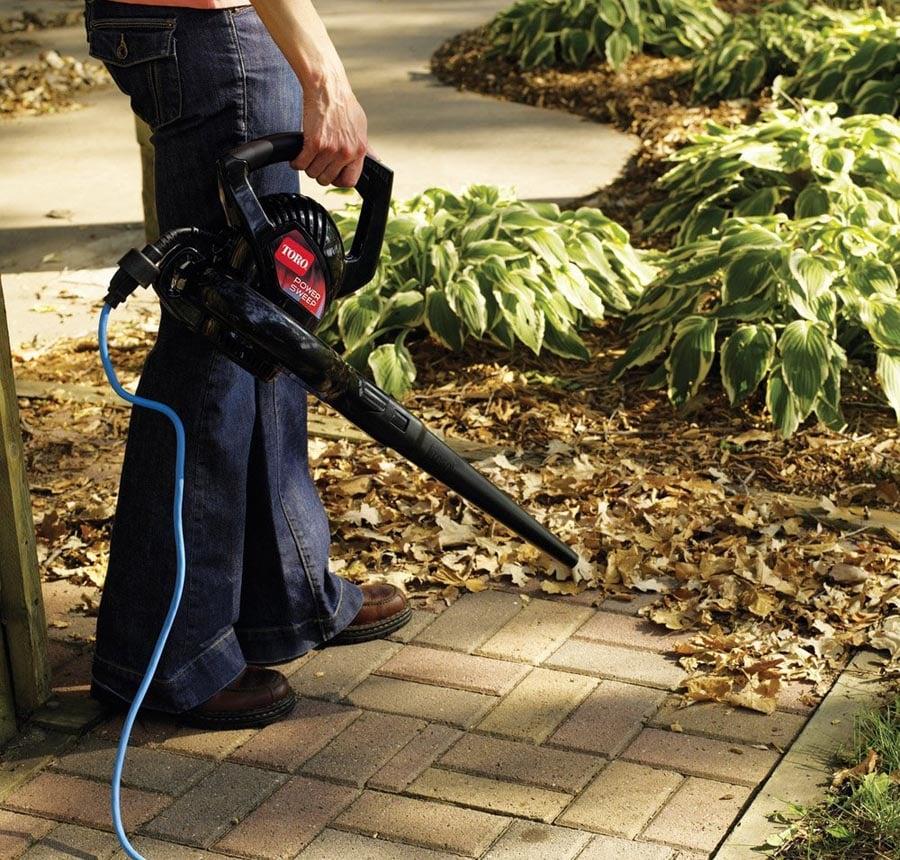 Man using leaf blower on side walk