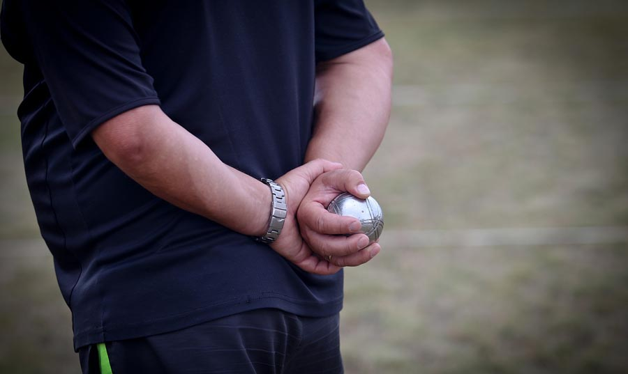 Man holding Bocce Ball behind his back