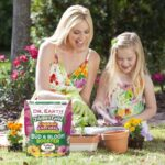 Mother and daughter with fertilizer and plants