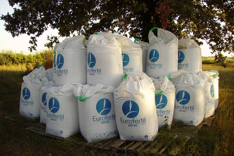 Bags of fertilizer stacked up in front of tree
