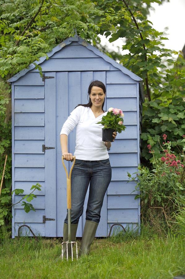 Lady with plant outside shed