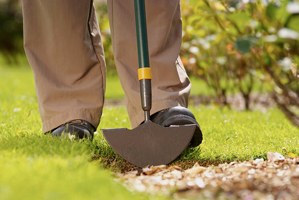 A man in steel-toe cap boots presses down onto a metallic lawn edger to excavate earth beneath it.